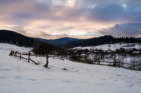 wooden fence along the snowy road. beautiful winter landscape of mountainous rural area at cloudy sunset Stock Photo