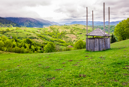 old wooden hay shed on grassy hillside. beautiful scenery of mountainous rural area in springtime Stock Photo