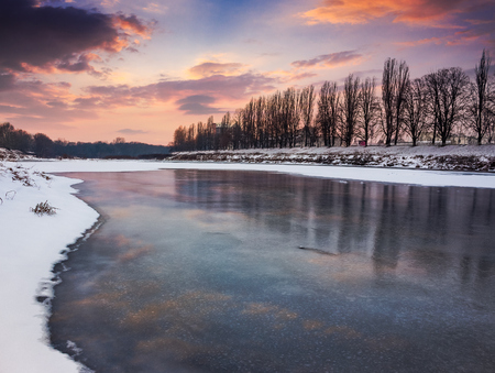 beautiful sunset on the frozen river. location Nealezhnosti embankment in Uzhgorod. beginning of the longest European linden alley in winter