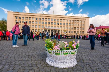 Uzhgorod, Ukraine - April 07, 2017: Celebrating Orthodox Easter in Uzhgorod on the Narodna square. Huge basket in front of  Transcarpathian Regional Administration building on a warm springtime day