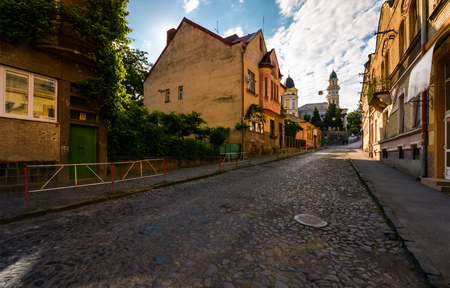 empty street of old town on summer morning. cobblestone pavement on the ground. beautiful scenery with architecture of Austria-Hungary times.