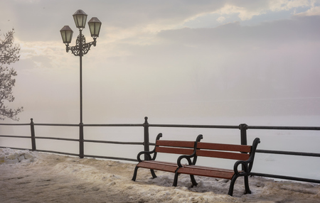 bench and lantern on foggy winter morning. location Nezalezhnosti embankment Uzhgorod, Ukraine