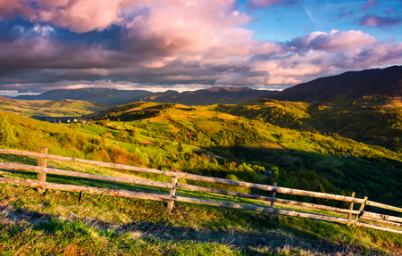 gorgeous evening in mountainous rural area. fence along the grassy slope. mountain ridge under the purple clouds on a blue sky. lovely landscape in fine springtime weather