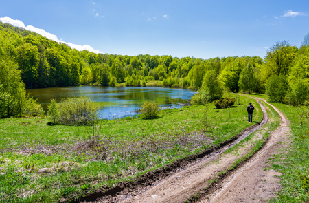 landscape with lake among the forest. countryside road down the hill. photographer observes beautiful scenery in mountains. fine springtime weather Stock Photo