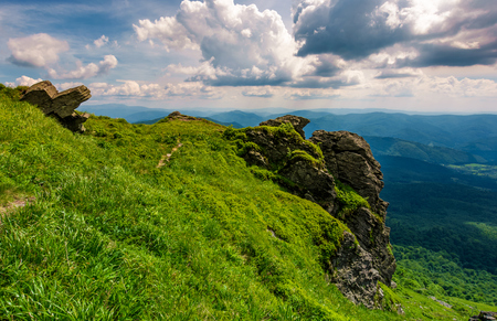grassy hillside over the cliff in mountains. beautiful mountain ridge in the distance. viewing location mountain Pikui. gorgeous landscape of Carpathians