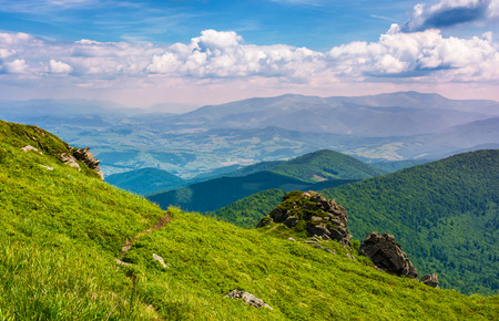 path through grassy hillside over the cliff in mountains. magnificent Borzhava mountain ride in the distance. viewing location mountain Pikui. gorgeous landscape of Carpathians Stock Photo