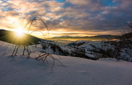 山岳農村地域の冬の日の出。村の雪が丘に覆われていた。遠くにゴージャスな光と山の尾根
