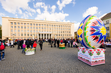 Uzhgorod, Ukraine - April 07, 2017: Celebrating Orthodox Easter in Uzhgorod on the Narodna square. Huge egg and basket of flowers in front of  Transcarpathian Regional Administration building on a warm springtime day
