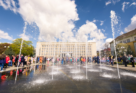Uzhgorod, Ukraine - April 07, 2017: Celebrating Orthodox Easter in Uzhgorod on the Narodna square. Fountain in front of  Transcarpathian Regional Administration building on a warm springtime day Editorial