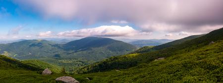 美しい山の風景のパノラマ。丘の上に雲が来る美しい景色 写真素材
