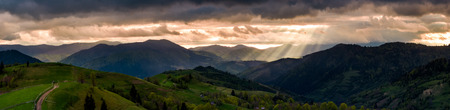 panorama of mountainous countryside at sunset. country road through rolling hills in to the distance. heavy clouds over the ridge. beams of lite from the heaven. beautiful and mysterious landscape Stock Photo