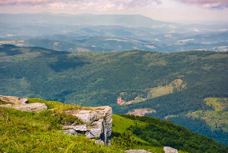 丘が転がる谷の上の岩の崖。深い視点を持つ美しい山岳風景 写真素材