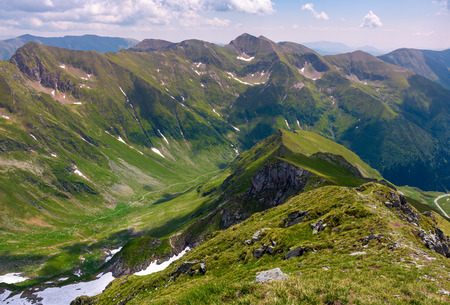 ridge with grassy slopes and cliffs. Southern Carpathian mountains in a far distance. beautiful summer scenery of Romania