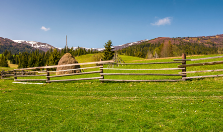 beautiful rural scenery in springtime. wooden fence and haystack on a grassy hillside at the foot of Borzhava mountain ridge with snowy tops. Stock Photo - 97492025