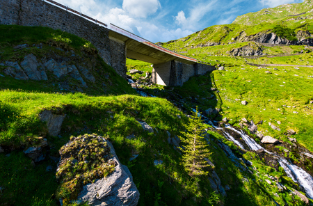 bridge over the brook in mountains. beautiful transportation scenery in summer landscape. location Transfagarasan rout of Romania Stock Photo