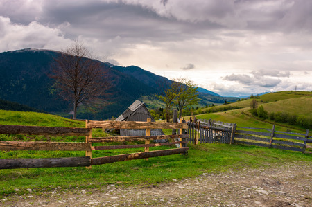 lovely rural landscape in Carpathians. wooden fence along the road on a cloudy day in mountains Stock Photo