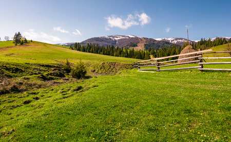 beautiful rural scenery in springtime. wooden fence and haystack on a grassy hillside at the foot of Borzhava mountain ridge with snowy tops. Stock Photo - 97521446