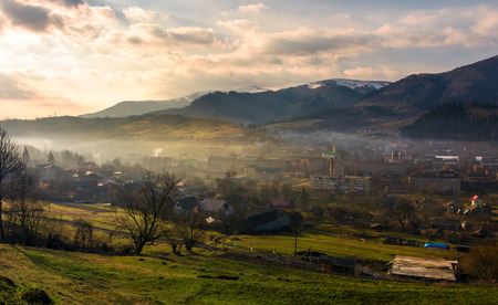 cloudy and foggy sunrise in Carpathian mountains. Small town Volovets in the valley at the foot of Borzhava mountain ridge with snowy tops. lovely springtime scenery Stock Photo - 97520769