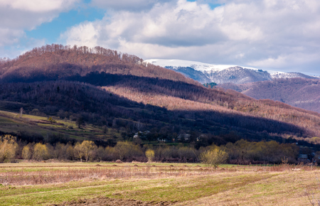 Lovely countryside landscape in springtime. mountain with snowy top in the distance. village at the foot of the mountain