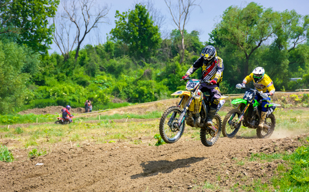 Uzhgorod, Ukraine - May 21, 2017: Extreme enduro MOTO SPORT. KTM racers turn on a corner in dirt. TransCarpathian regional Motocross Championship Stock Photo - 104911367