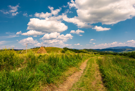 country road along the hillside. lovely countryside rural scenery in summer. beautiful blue summer sky with fluffy clouds
