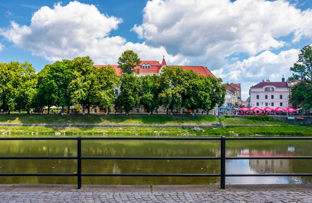 Uzhgorod, Ukraine - Jun 15, 2017: embankment of Uzh river in summer. Beautiful architecture and blossoming linden trees on fine weather day. Korzo street can be seen in the distance Editorial