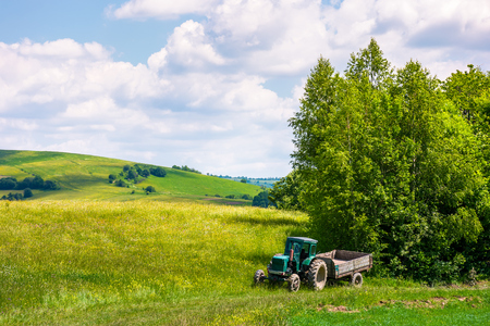 grassy fields on rolling hills in summer. beautiful countryside scenery in Carpathian mountains under the blue sky with white fluffy clouds. green tractor near the stands forest