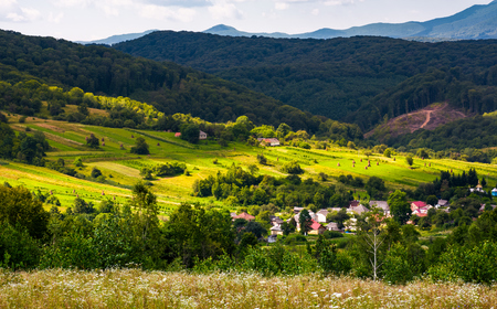 small Carpathian village in mountains. beautiful landscape with forested hills and agricultural fields