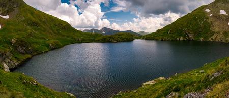 ルーマニア、カプラ湖のパノラマ。曇りの夏の日にファガラサン山脈の豪華な風景