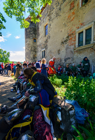 Chynadiyovo, Ukraine - May 27, 2017: medieval culture festival Silver Tatosh. Location St. Miklos Castle. Knight participants have rest under the castle wall in shade of tree Editorial
