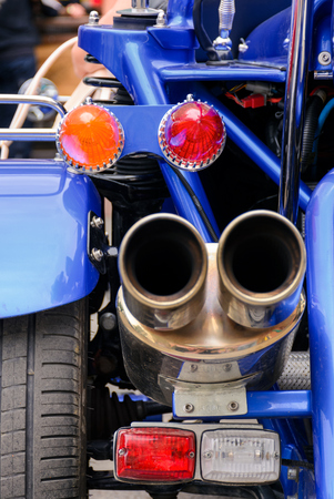back side of a blue motorcycle. lovely detail shot of lights and shiny exhaust pipes