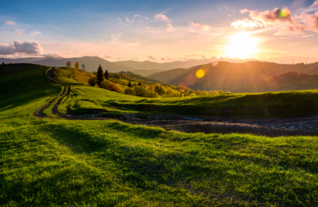 winding road along the grassy rural hill at sunset. gorgeous landscape of Carpathian mountain in springtime Stock Photo
