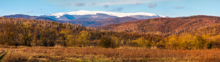springtime countryside with snowy mountain in the distance. lovely panorama of Runa mountain in evening Stock Photo