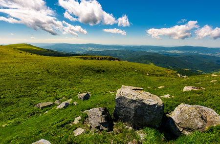 gorgeous mountain landscape on a summer day. giant boulders on a grassy hillside under the beautiful sky with clouds.