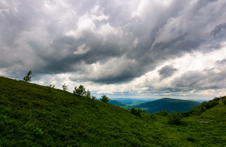mountain landscape in rainy weather. lovely summer scenery with grey menacing clouds over the grassy slope