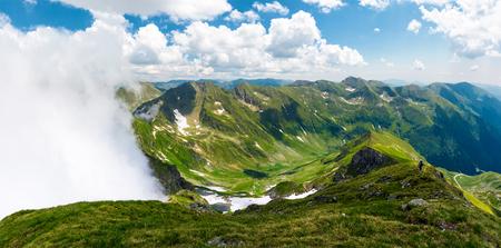 上昇雲と山岳パノラマ。草原の丘の中腹に雪が降る美しい風景。ルーマニアのファガラ山脈でのハイキングに人気の目的地