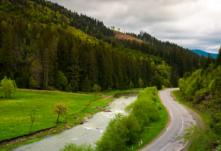 road along the river near the forest on hillside. lovely springtime landscape in mountains on a cloudy day. view from above Stock Photo