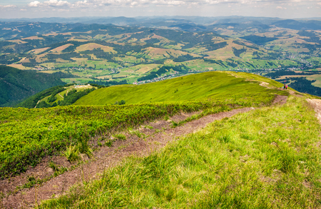 foot path down the grassy hillside. location mountain Gymba, TransCarpathia, Ukraine. tourists climbing hill in the distance. great summer outdoor activities Stock Photo - 98803286