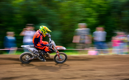 Uzhgorod, Ukraine - May 21, 2017: Junior MX rider turns on a corner. Motion blur with flying dirt. TransCarpathian regional Motocross Championship