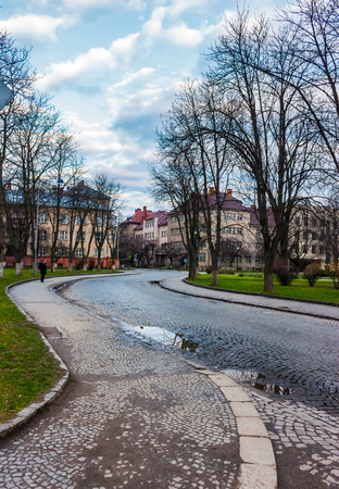 cobble street winding through old town. lovely cityscape in springtime. location Narodna square, Uzhgorod, Ukraine. Foto de archivo