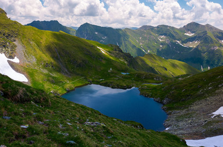 lake Capra in Fagarasan mountains of Romania. beautiful summer scenery on a cloudy day. Popular tourist destination for Hiking. Stock Photo