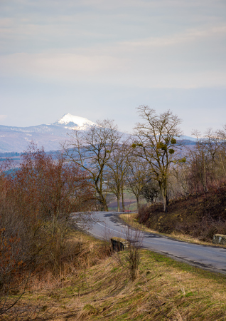 country road in to the mountains with snowy peak. lovely transportation background in springtime Stock Photo