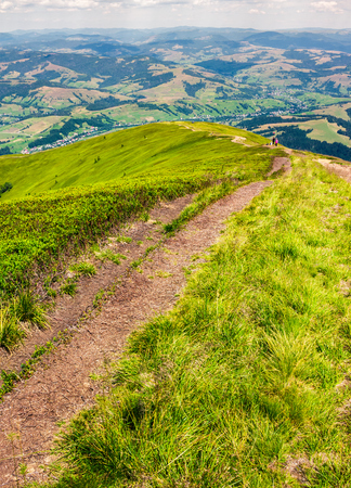 foot path down the grassy hillside. location mountain Gymba, TransCarpathia, Ukraine. tourists climbing hill in the distance. great summer outdoor activities Stock Photo - 98821401