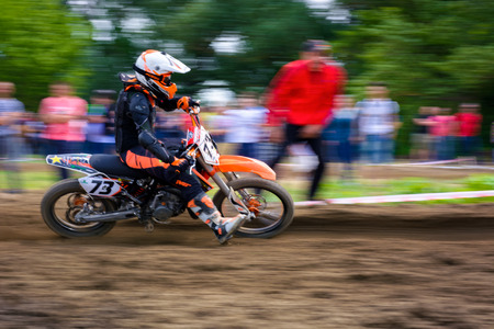 Uzhgorod, Ukraine - May 21, 2017: MX rider turns on a corner. Motion blur with flying dirt. TransCarpathian regional Motocross Championship Stock Photo - 98811217