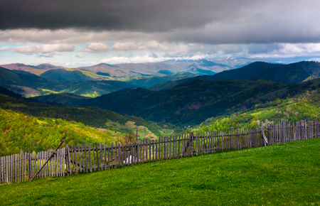 fence on the edge of the hillside. beautiful rural landscape of Carpathian mountains in springtime. forested hills under the heavy clouds in the distance Stock Photo