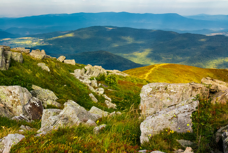 huge rocky formations on the grassy hills. beautiful mountain landscape in late summer on a cloudy day. location Runa mountain, Ukraine Stock Photo - 99265254
