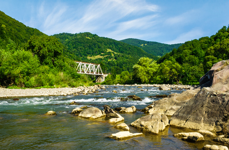 river in forested mountains. beautiful summer landscape with huge rocks on the shore and a white metal train bridge in the distance Stock Photo