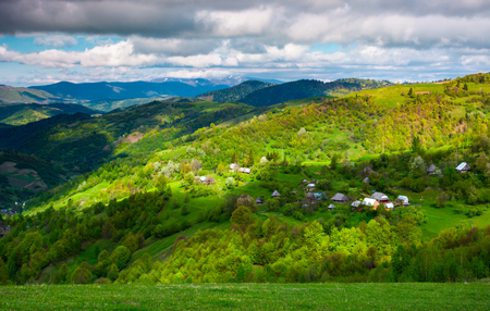 village on a forested hillside in springtime. beautiful rural scenery of Carpathian mountains on a cloudy day Stock Photo