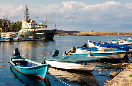 SOZOPOL - AUGUST 19: fishing boats at sunset on August 19, 2015 in Sozopol, Bulgaria. small fishing boats and few big one docked near embankment in port of Bulgarian town Sozopol in evening light