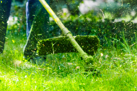 Gras schneiden im Garten mit Trimmer. reizender Naturhintergrund Standard-Bild - 99578653